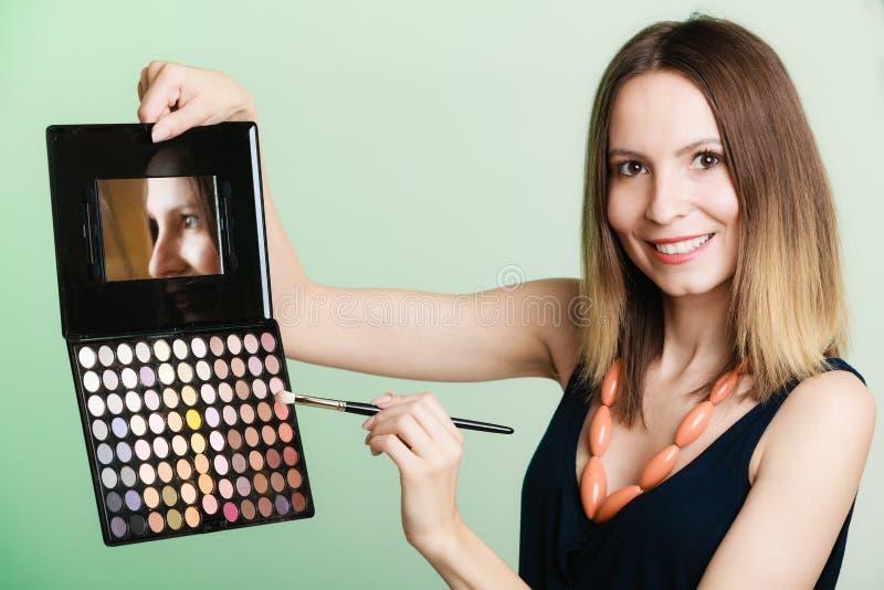La mujer sostiene la paleta y el cepillo profesionales del maquillaje fotografía de archivo libre de regalías