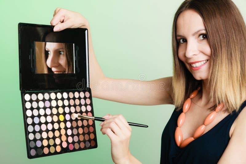 La mujer sostiene la paleta y el cepillo profesionales del maquillaje fotos de archivo libres de regalías