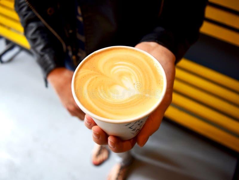 La mujer sostiene la taza de café con el corazón imagenes de archivo