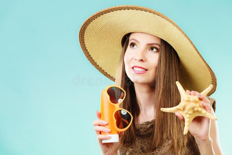 La mujer sostiene las gafas de sol y la loci?n de la protecci?n solar fotos de archivo