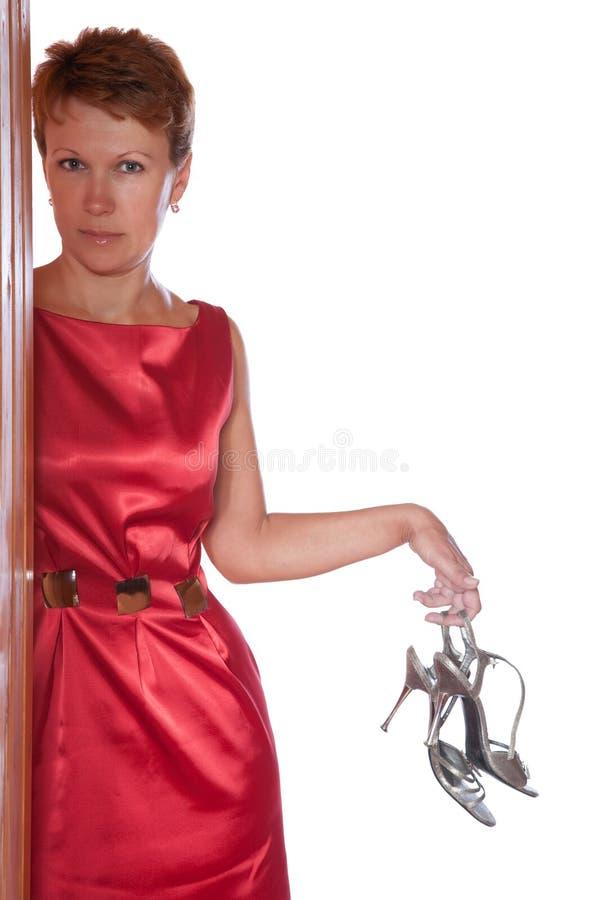 La mujer sostiene los zapatos con un alto talón imágenes de archivo libres de regalías