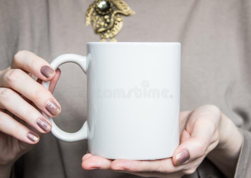 La mujer sostiene la taza blanca en manos Maqueta del diseño imagenes de archivo
