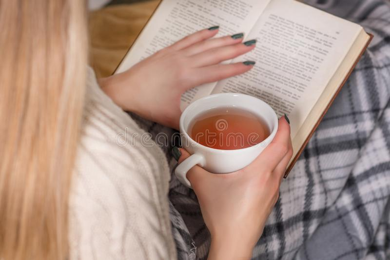 La mujer sostiene la taza caliente de libro del té y de lectura en cama fotografía de archivo libre de regalías