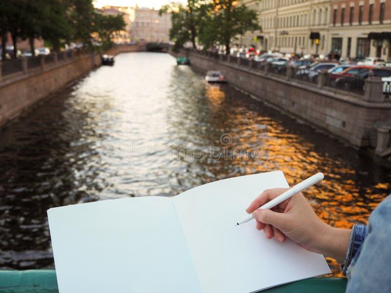 La mujer sostiene un diario blanco mientras que se coloca en el puente en el fondo del río de la ciudad imagenes de archivo
