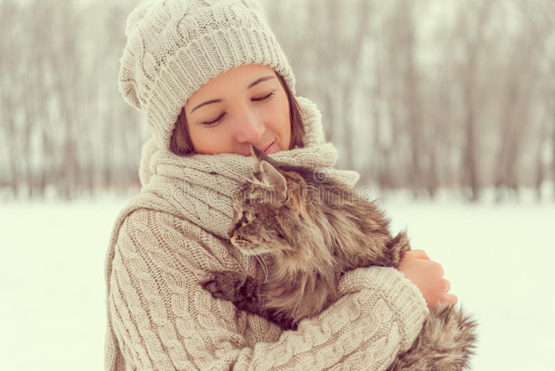 La mujer sostiene un gato en la naturaleza fotografía de archivo libre de regalías