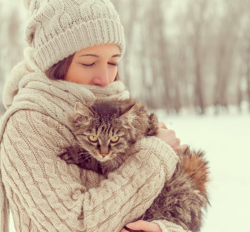 La mujer sostiene un gato en la naturaleza fotografía de archivo