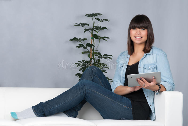 La mujer sostiene una tableta foto de archivo
