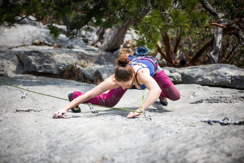 La mujer sube una roca foto de archivo
