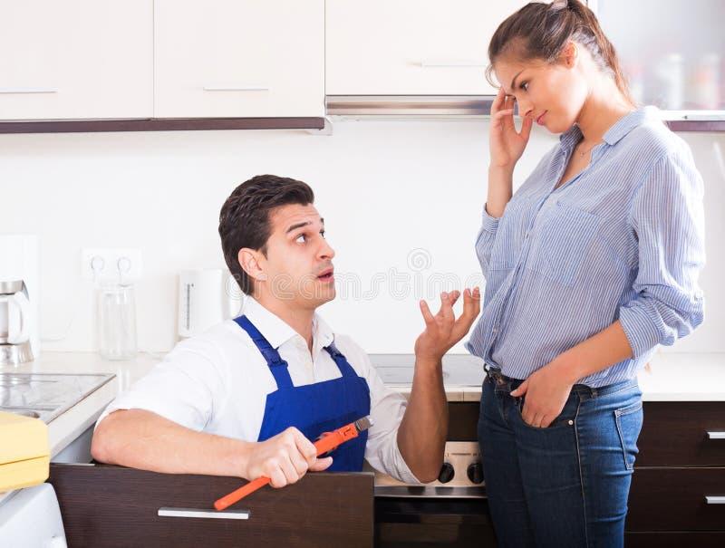 La mujer subrayada y las manitas nerviosas acercan al fregadero en cocina imágenes de archivo libres de regalías