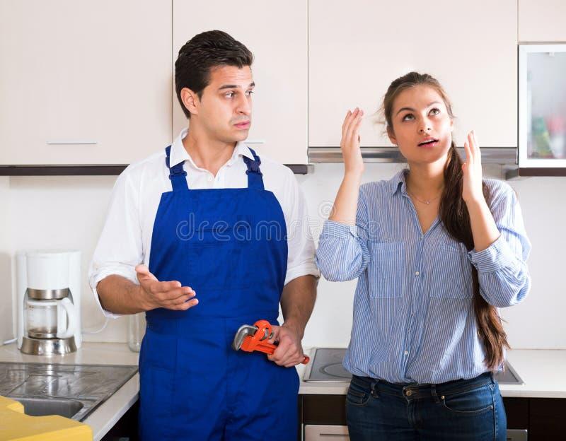 La mujer subrayada y las manitas nerviosas acercan al fregadero en cocina foto de archivo