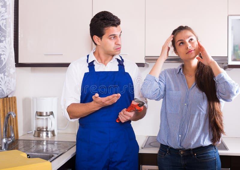 La mujer subrayada y las manitas nerviosas acercan al fregadero en cocina foto de archivo libre de regalías