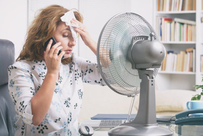 La mujer sufre de calor en la oficina o en casa imagenes de archivo