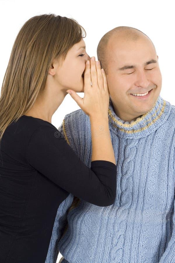 La mujer susurra en un oído al hombre joven foto de archivo libre de regalías