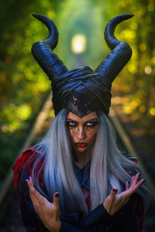 La mujer terrible con maquillaje asombroso de cuernos del pelo negro de la plata en el túnel del bosque con los carriles se cierr imágenes de archivo libres de regalías
