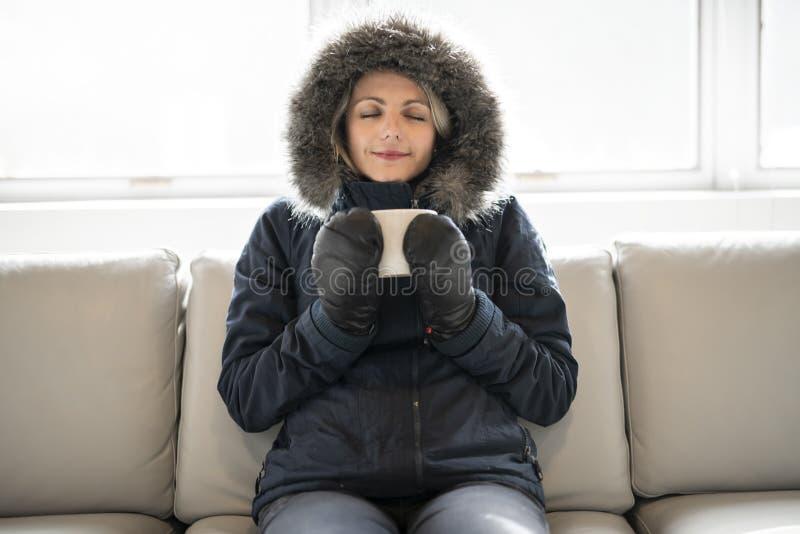 La mujer tiene café frío de la bebida en el sofá en casa con el abrigo de invierno imagen de archivo