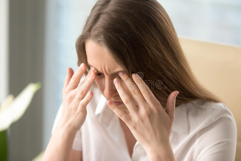 La mujer tiene dolor de cabeza debido a trabajo excesivo crítico imagen de archivo libre de regalías