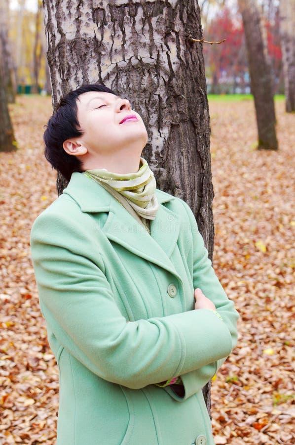 La mujer tiene un resto en parque del otoño imagen de archivo