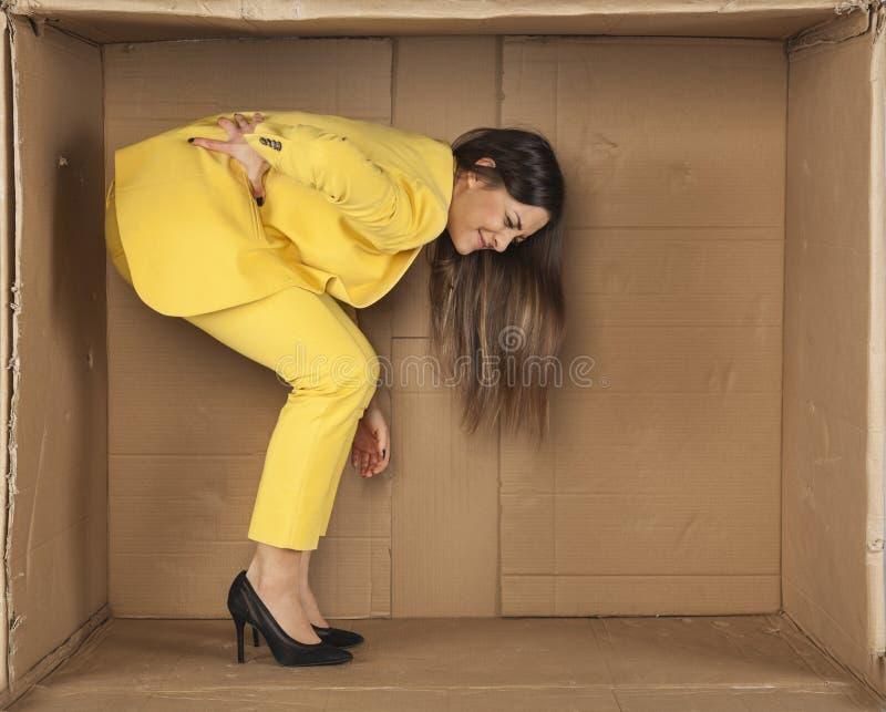 La mujer tiene una parte posterior dolorida de permanecer en un cuarto encogido fotografía de archivo libre de regalías