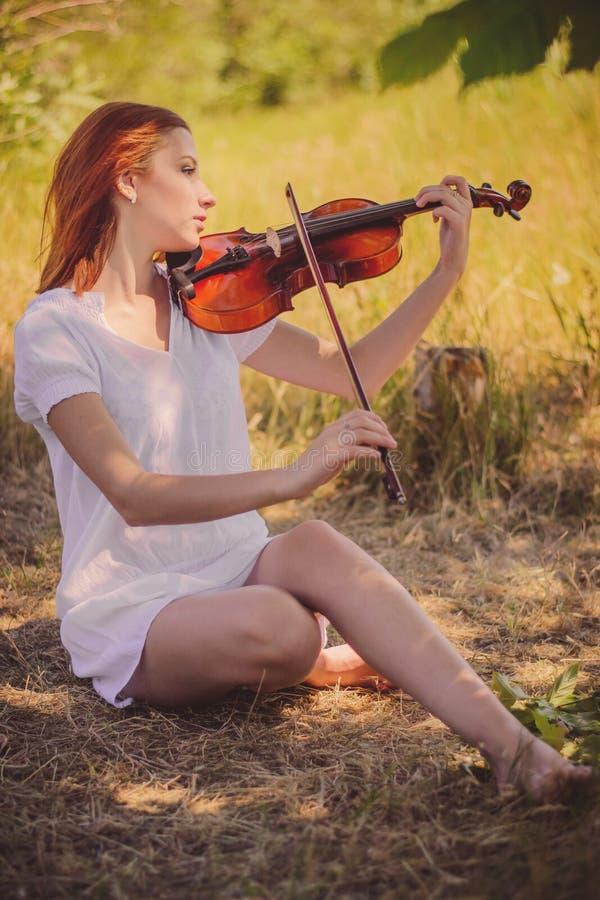 La mujer toca el violín foto de archivo libre de regalías