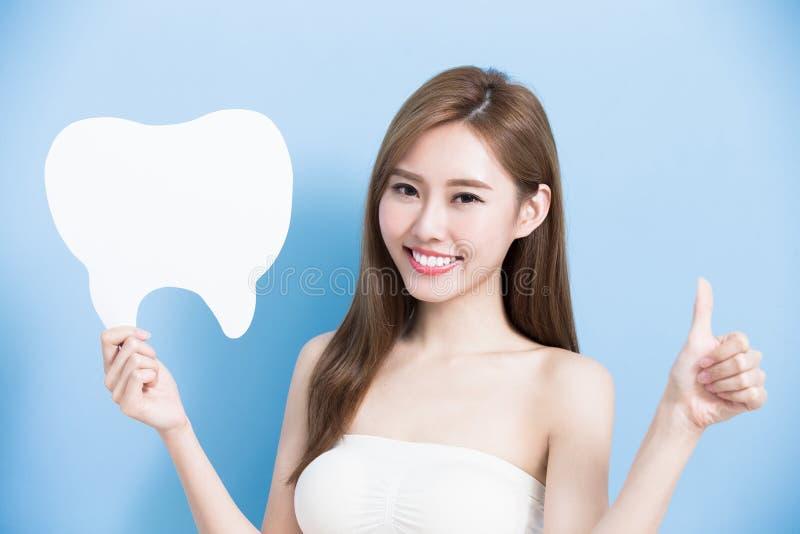 La mujer toma el diente lindo fotos de archivo