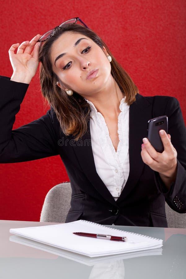La mujer toma imágenes en su teléfono foto de archivo libre de regalías