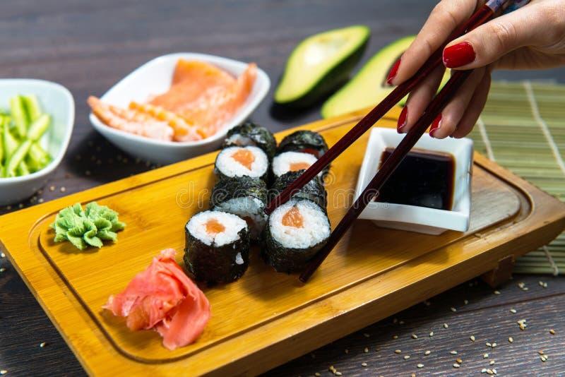La mujer toma los rollos de sushi usando los palillos imagenes de archivo