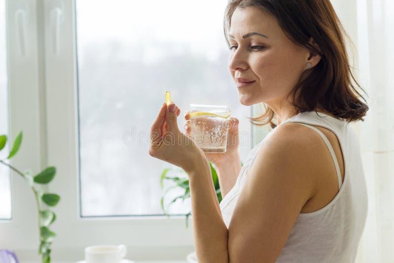 La mujer toma la píldora con omega-3 y sostener un vidrio de agua dulce con el limón Imagen de la casa, por la mañana cerca de la fotografía de archivo libre de regalías