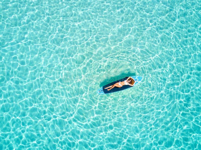 La mujer toma un sunbath en una tabla hawaiana sobre las aguas tropicales de los Maldivas fotos de archivo