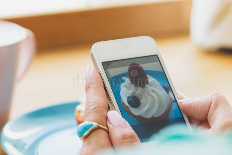 La mujer toma una imagen de la taza con café y una magdalena en la placa fotos de archivo