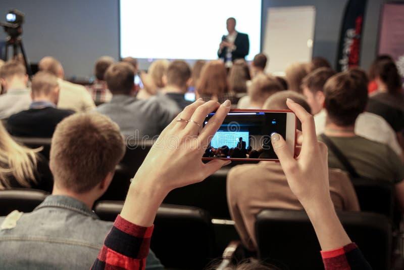 La mujer toma una imagen durante la conferencia usando smartphone imagen de archivo