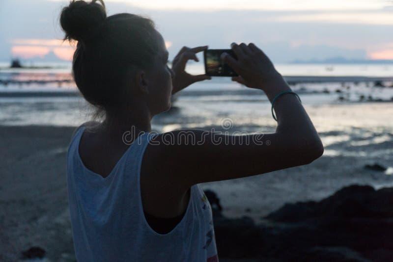 La mujer toma una puesta del sol sobre el mar en una cámara del teléfono imagenes de archivo