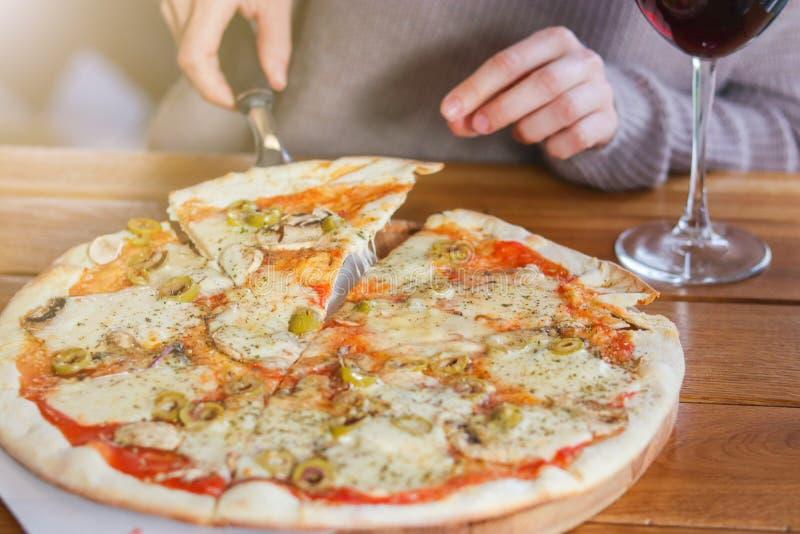 La mujer toma una rebanada de pizza cortada con la mozzarella imagen de archivo