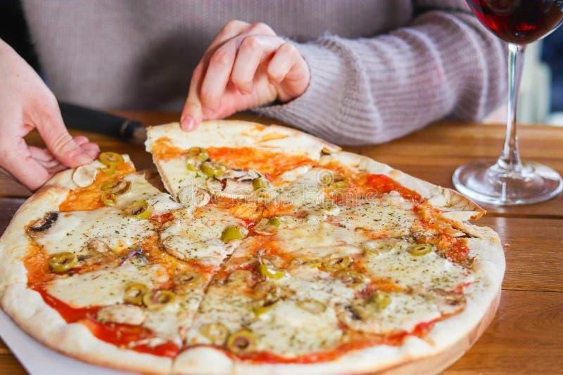 La mujer toma una rebanada de pizza cortada fotos de archivo libres de regalías