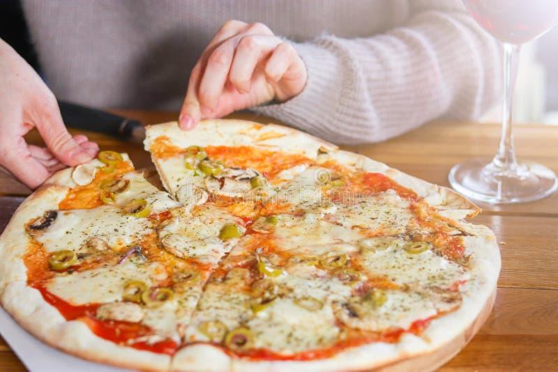 La mujer toma una rebanada de pizza cortada con zha imagen de archivo