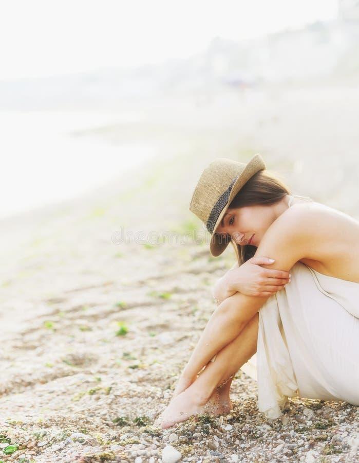 La mujer tranquila joven relaja sentarse en una playa del mar de la arena, mañana de niebla romántica imagen de archivo