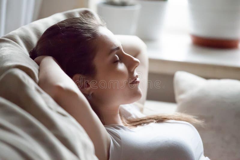La mujer tranquila que se relaja en el sofá da gastos indirectos foto de archivo
