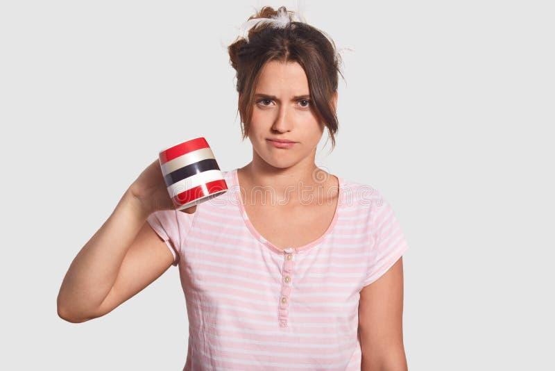La mujer trastornada del descontento en pijamas limita la taza, demuestra que ella no tiene ningún café a beber, necesita entrar  imagenes de archivo