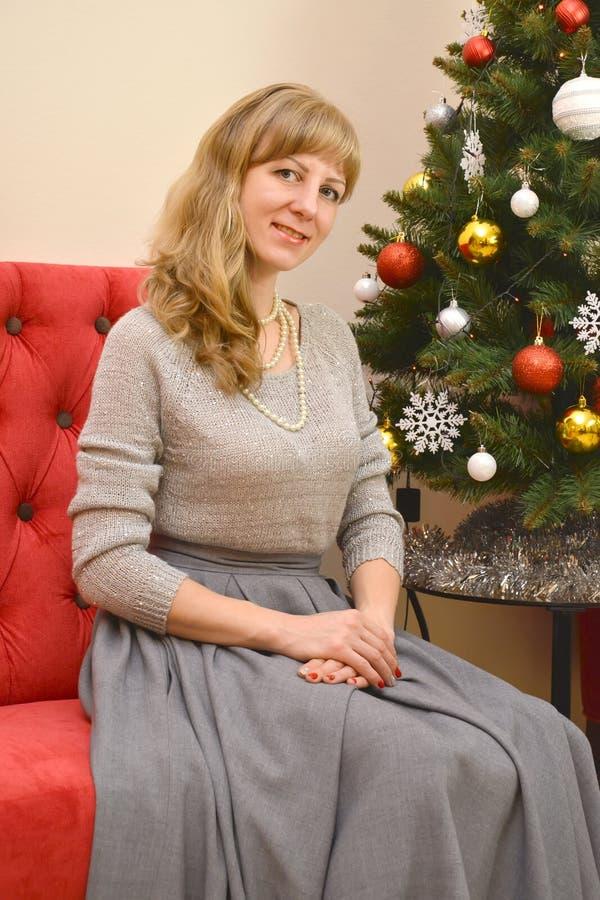 La mujer treinta-año-vieja se sienta en un sofá rojo sobre un árbol del Año Nuevo fotos de archivo