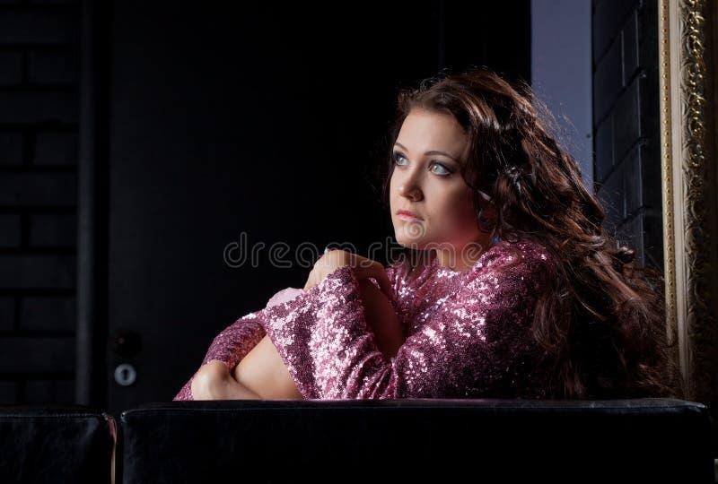 La mujer triguena bonita asustada se sienta en el sofá negro imagen de archivo