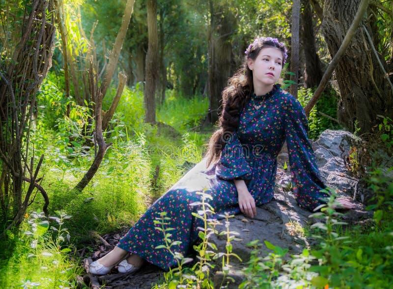 La mujer triste joven se sienta en una piedra por un árbol en un bosque foto de archivo libre de regalías