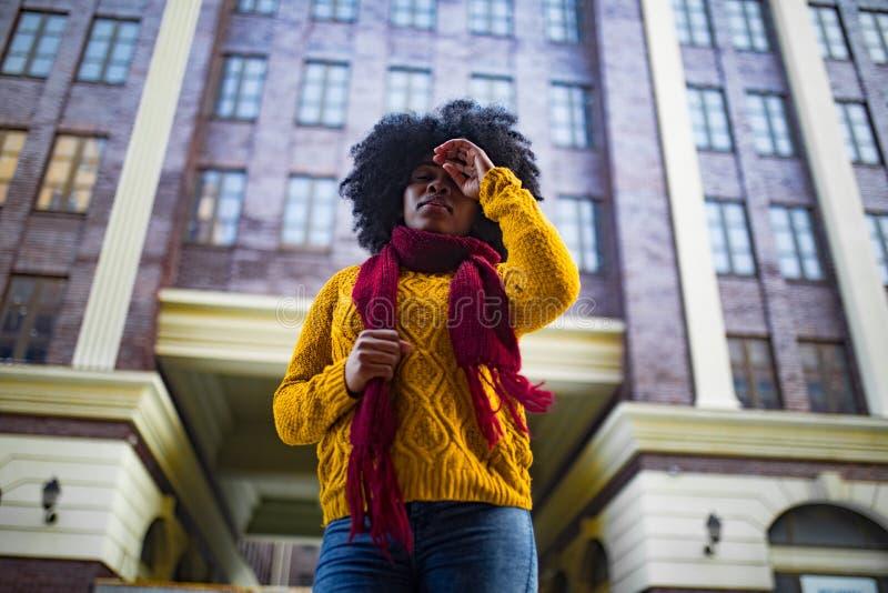 La mujer triste negra joven se está oponiendo al fondo del edificio imágenes de archivo libres de regalías
