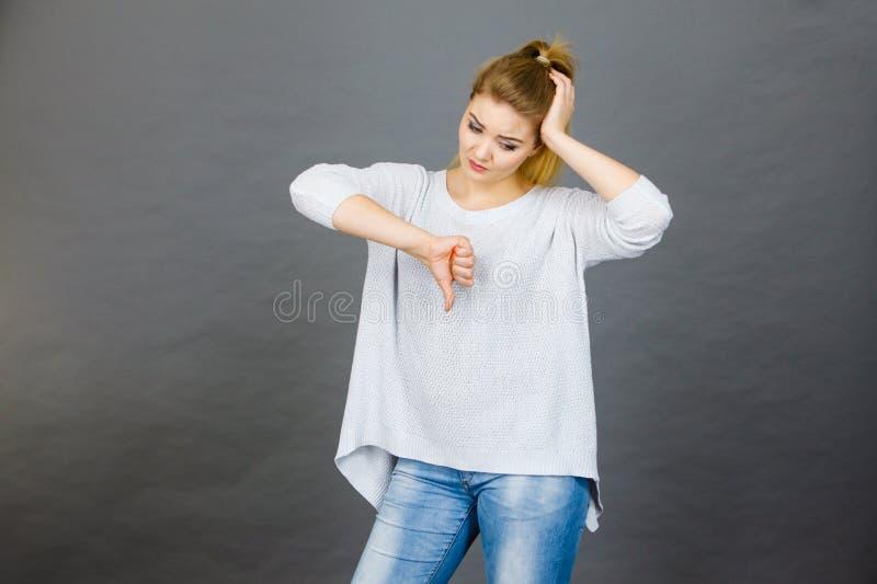 La mujer triste que muestra el pulgar abajo gesticula imagen de archivo