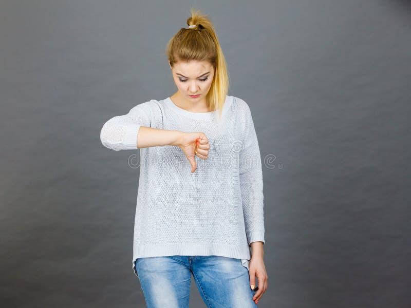 La mujer triste que muestra el pulgar abajo gesticula foto de archivo