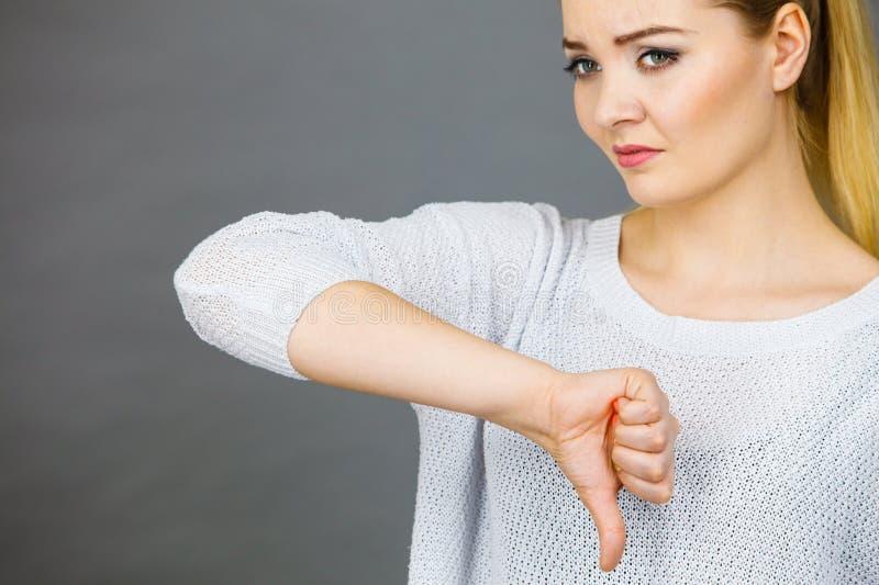 La mujer triste que muestra el pulgar abajo gesticula imagen de archivo libre de regalías