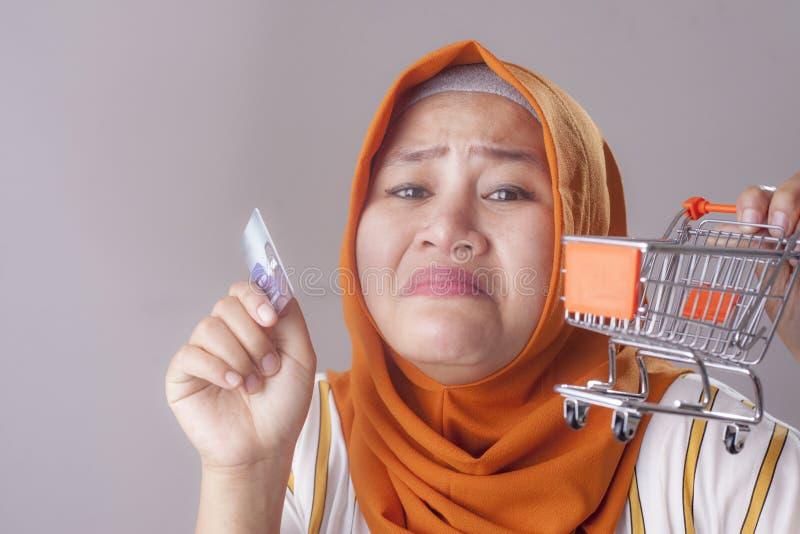 La mujer triste sostiene la tarjeta de cr?dito, concepto de la quiebra fotos de archivo