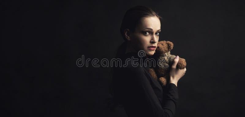 La mujer triste sostiene un juguete del oso de peluche foto de archivo