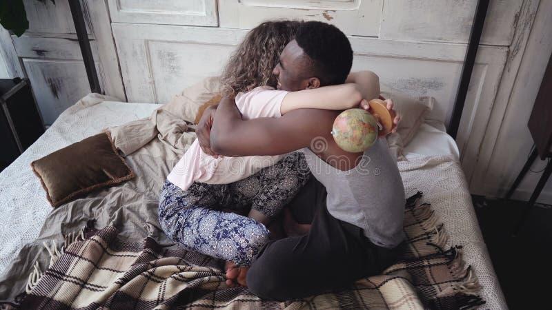 La mujer tuerce el globo, selecciones del hombre la ubicación a viajar Los pares multirraciales en pijamas disfrutan, abrazan y s foto de archivo