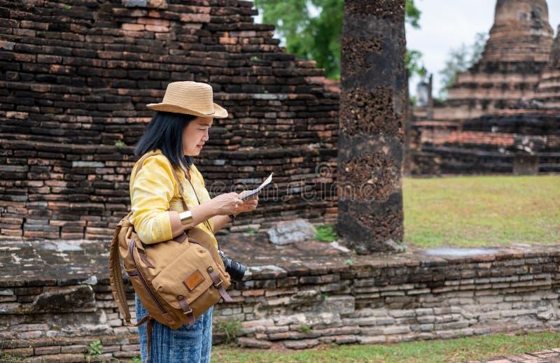 La mujer turística asiática ve el mapa en antiguo de la arquitectura tailandesa del templo de la pagoda en Sukhothai, Tailandia V fotografía de archivo libre de regalías