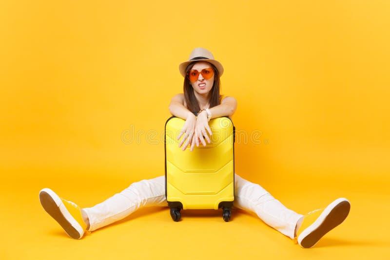 La mujer turística en ropa casual del verano, sombrero del viajero triste se sienta cerca de la maleta en fondo amarillo-naranja  fotografía de archivo