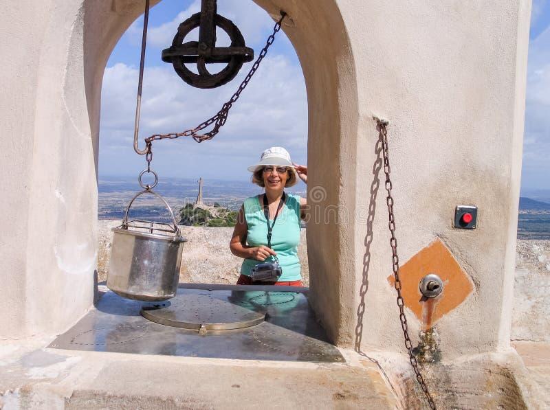 La mujer turística madura feliz permanece cerca de pozo de drenaje viejo imagen de archivo libre de regalías